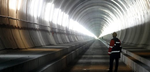 A visitor stands at the Erstfeld-Amsteg section of the NEAT Gotthard Base Tunnel October 5, 2010. With a length of 57 km (35 miles) crossing the Alps, the world's longest train tunnel should become operational at the end of 2017. REUTERS/Arnd Wiegmann (SWITZERLAND - Tags: BUSINESS CONSTRUCTION TRANSPORT TRAVEL IMAGES OF THE DAY)