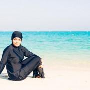 Young-woman-wearing-burkini-sitting-by-the-beach-in-dubai